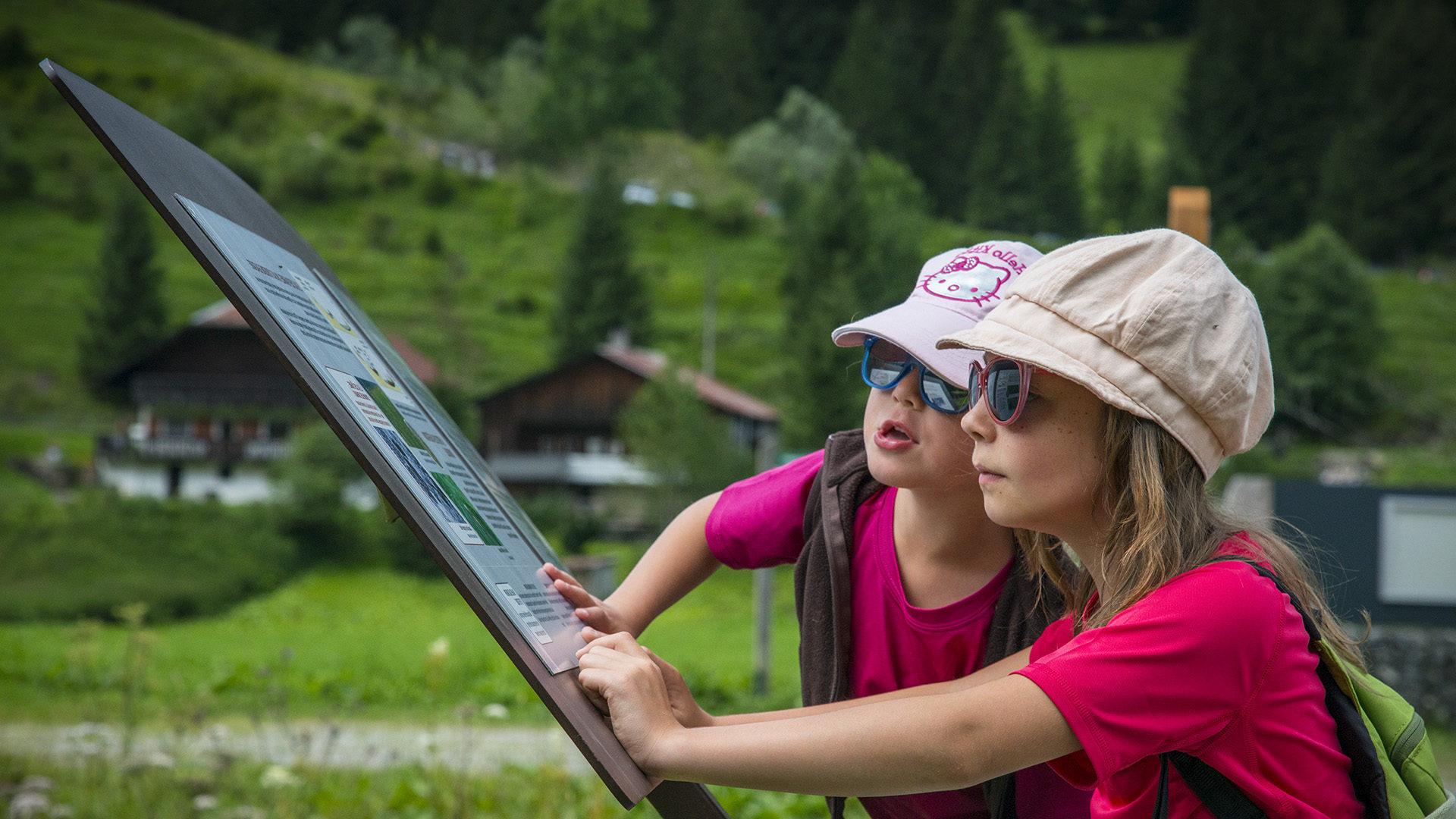 2 écoliers lisent un panneau du Géoparc au lac des Plagnes
